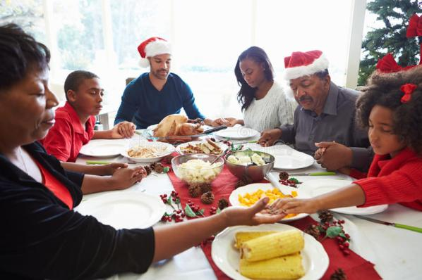 multi-generation-family-praying-christmas-meal-holding-hands-eyes-closed-35791389